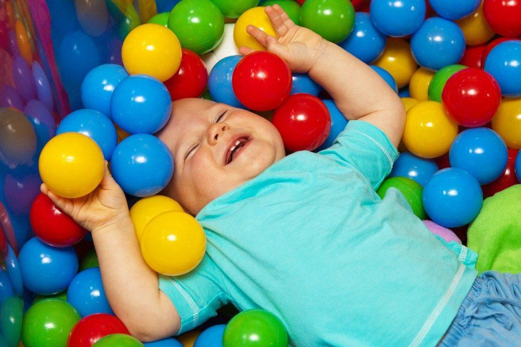 bébé avec boules dans grande piscine à balle